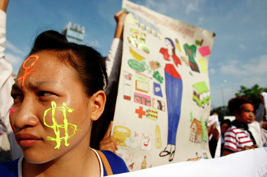 A Cambodian garment factory worker, left, is her face painted with the U.S. currency sign as she joins a rally on May Day in Phnom Penh, Cambodia, Wednesday, May 1, 2013. They demand the government an increase in wages and better working condition. (AP Photo/Heng Sinith) / AP