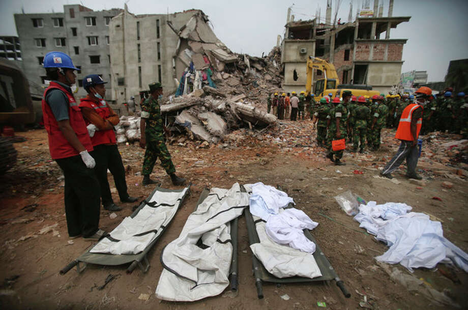 Stretchers with a body bags are placed on standby while workers toil in the collapsed garment factory building, Tuesday, April 30, 2013 in Savar, near Dhaka, Bangladesh. Emergency workers hauling large concrete slabs from a collapsed 8-story building said Tuesday they expect to find many dead bodies when they reach the ground floor, indicating the death toll will be far more than the official 386. One estimate said it could be as high as 1,400. The illegally constructed, 8-story Rana Plaza collapsed on the morning of April 24, bringing down the five garment factories inside.(AP Photo/Wong Maye-E) / AP