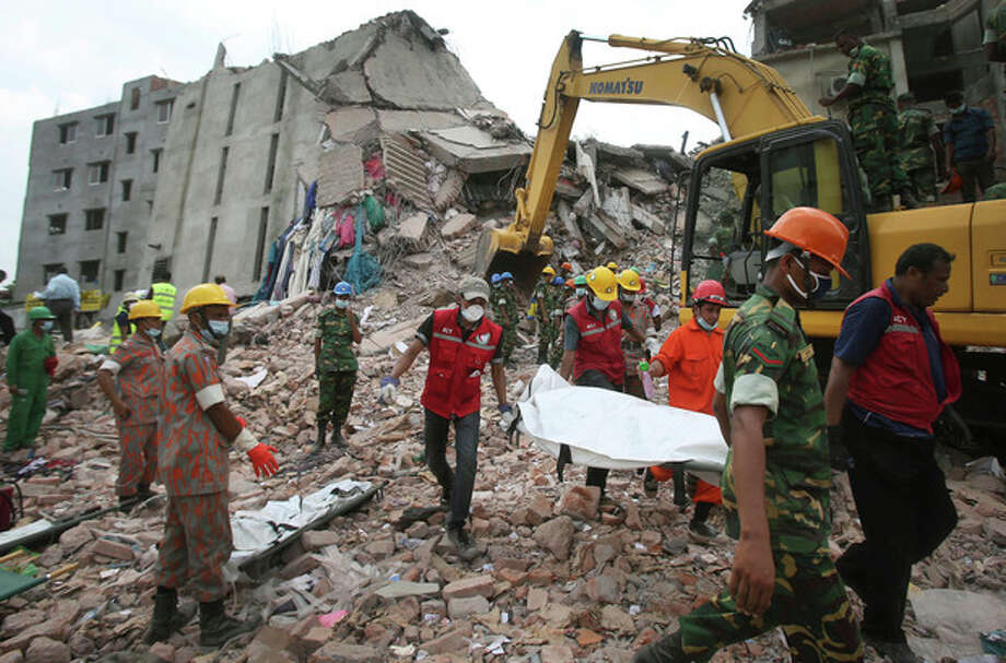 Workers carry a body that was trapped for almost a week in a collapsed garment factory building on Tuesday, April 30, 2013 in Savar, near Dhaka, Bangladesh. Emergency workers hauling large concrete slabs from the collapsed eight-story building said Tuesday they expect to find many dead bodies when they reach the ground floor. (AP Photo/Wong Maye-E) / AP