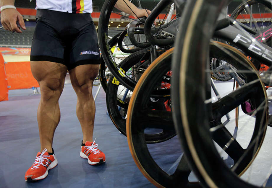 In this Thursday, July 26, 2012 photo, Robert Foerstemann of Germany stands next to his bike as he arrives for a men's cycling training session at the 2012 Summer Olympics, in London. The superhuman bodies of many of the men and women competing in the games can be a stark reminder of how far the rest of us have fallen. (AP Photo/Christophe Ena) / AP