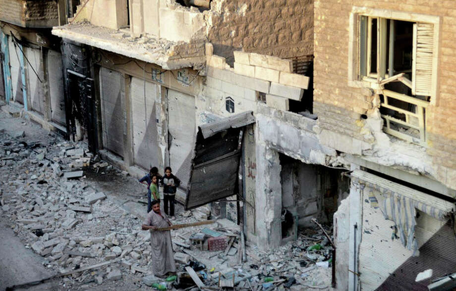 In this citizen journalism image taken on Saturday, July 28, 2012 and provided by Edlib News Network ENN, a Syrian family stand in the rubble of destroyed houses in Maarat al-Numaan on the eastern edge of Idlib province, northern Syria. (AP Photo/Edlib News Network ENN) THE ASSOCIATED PRESS IS UNABLE TO INDEPENDENTLY VERIFY THE AUTHENTICITY, CONTENT, LOCATION OR DATE OF THIS HANDOUT PHOTO / EDLIB NEWS NETWORK ENN