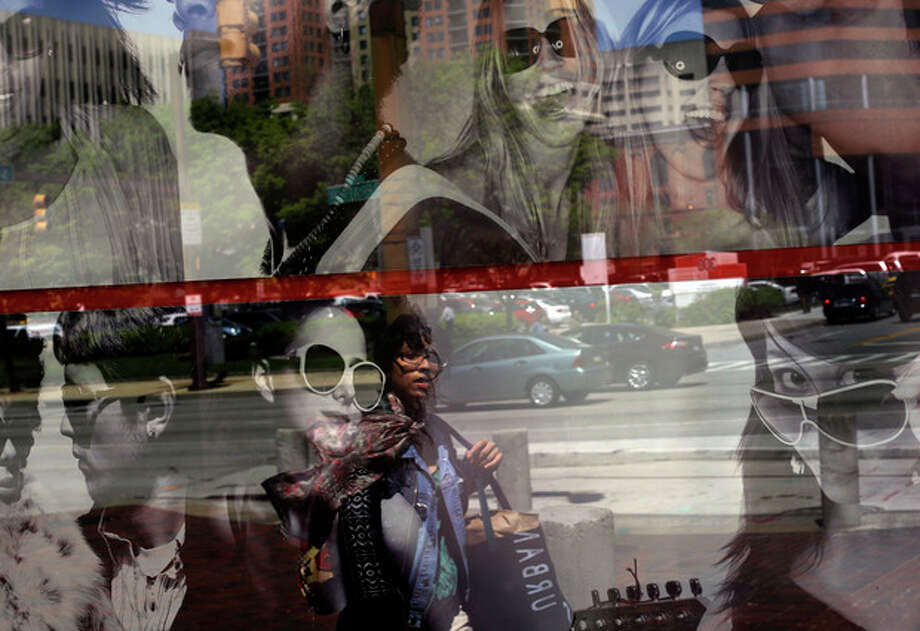 In this April 25, 2013 photo, a woman is reflected in a retail store's window display in Baltimore. The private Conference Board reports on consumer confidence for April on Tuesday, April 30, 2013.(AP Photo/Patrick Semansky) / AP