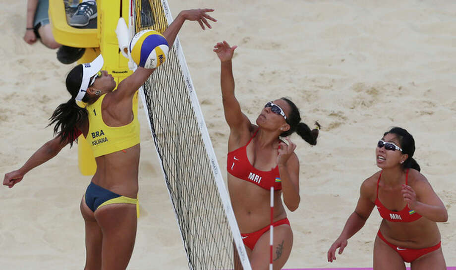 Juliana Silva, left, from Brazil tries to block Elodie Li Yuk Lo, right, and Natacha Rigobert, center, both from Mauritius during their Beach Volleyball match at the 2012 Summer Olympics, Saturday, July 28, 2012, in London. (AP Photo/Petr David Josek) / AP
