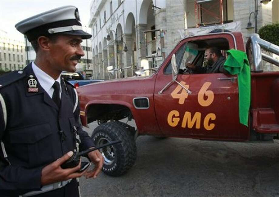 A police officer smiles at the sight of a jacked up 4x4 car near Green Square in Tripoli, Libya, Monday March 21, 2011. The normally busy streets of Tripoli are quiet, as International forces continued air strikes against Libya forces on Monday. (AP Photo/Jerome Delay)