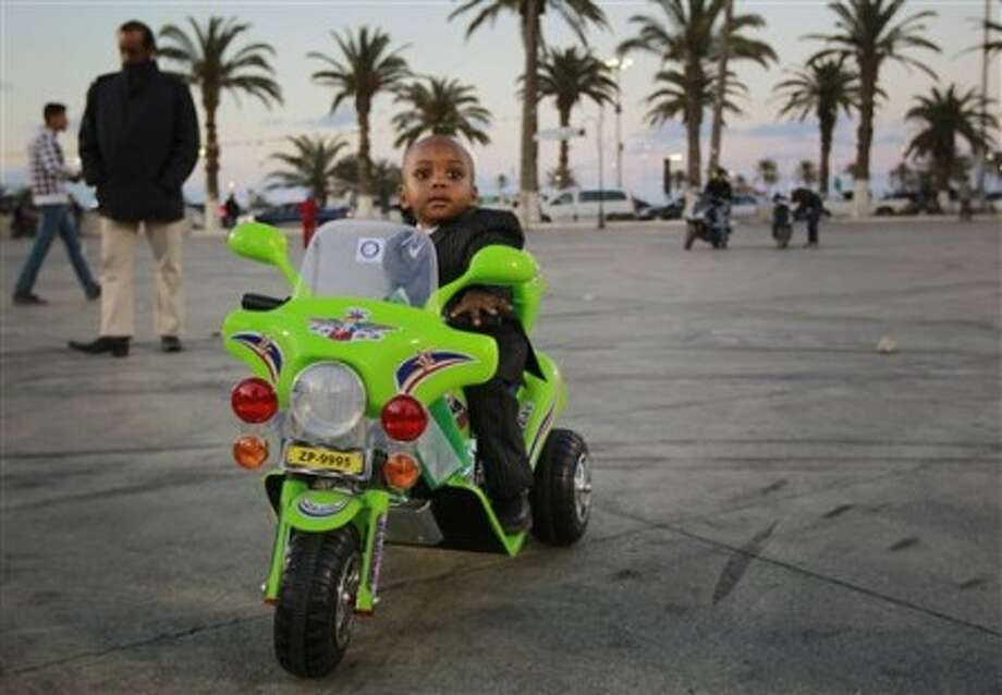 Two-year old Mohammed, dressed in a suit as he rides his toy Harley on Green Square in Tripoli, Libya, Monday March 21, 2011. International forces continued air strikes against Libya on Monday, moving to expand the U.N.-approved no-fly zone after turning back government troops near the eastern rebel stronghold of Benghazi, the U.S. commander in the region said. (AP Photo/Jerome Delay)