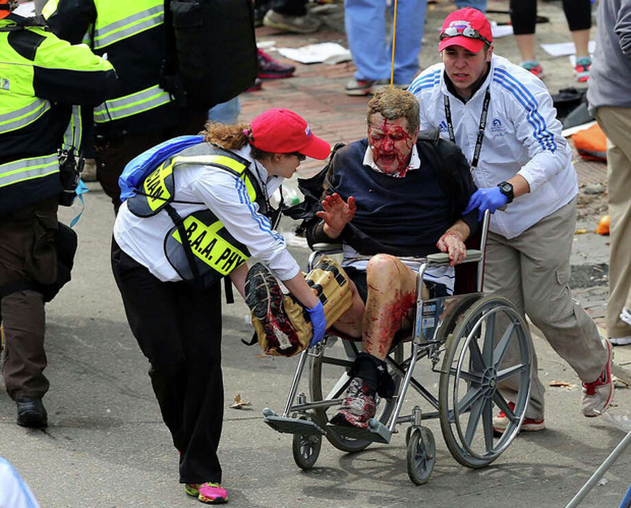 Medical workers aid an injured man at the 2013 Boston Marathon following an explosion in Boston, Monday, April 15, 2013. Two bombs exploded near the finish of the Boston Marathon on Monday, killing at least two people, injuring at least 22 others and sending authorities rushing to aid wounded spectators. (AP Photo/The Boston Globe, David L. Ryan) MANDATORY CREDIT / The Boston Globe