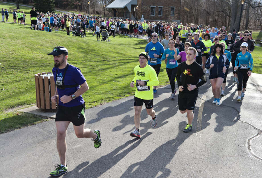 Brett Beier, left, leads the Solidarity run he organized to honor the victims of the Boston Marathon bombing, Tuesday, April 16, 2013, in Kalamazoo, Mich. (AP Photo/Kalamazoo Gazette-MLive Media Group, Erik Holladay) ALL LOCAL TV OUT; LOCAL TV INTERNET OUT