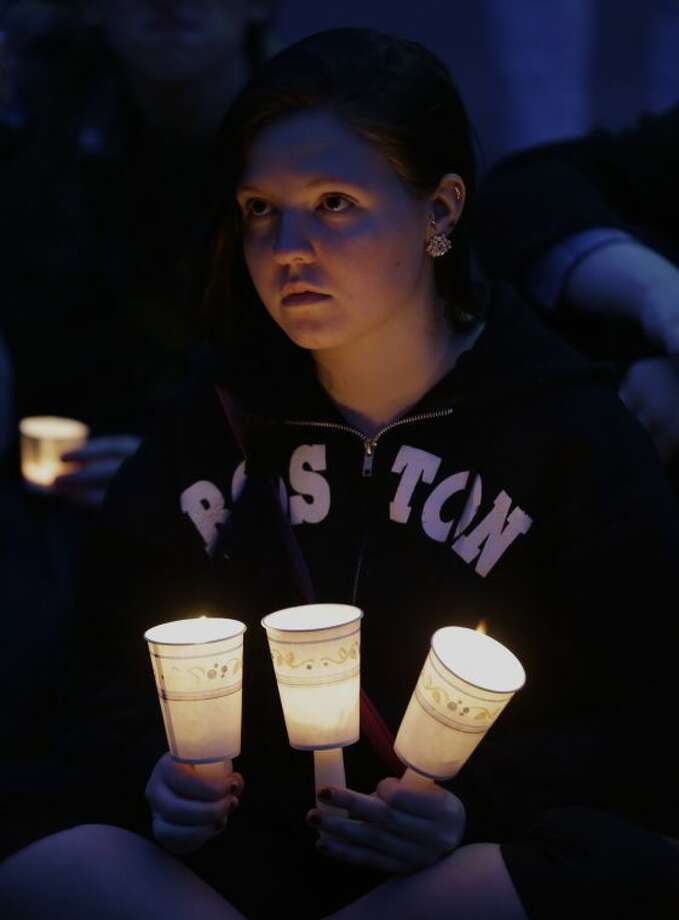 Bridget Wood, 18, of Boston, holds candles during a vigil the victims of the Boston Marathon explosions at Boston Common, Tuesday, April 16, 2013. (AP Photo/Julio Cortez)