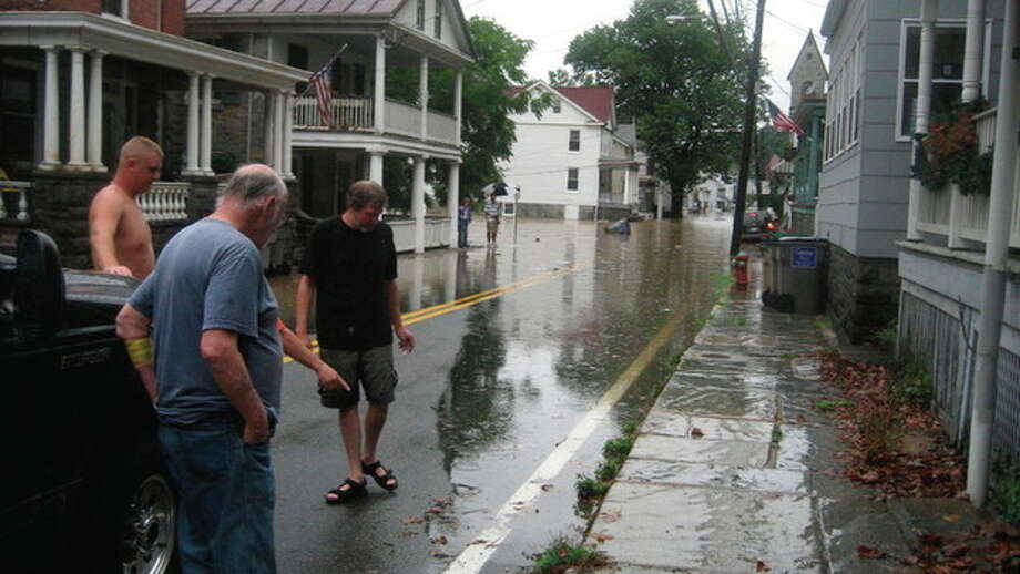 John Blackburn, second left, watches with neighbors as floodwater rises on Main Street in Port Deposit, Md. Thursday, Sept. 8, 2011. The waters were expected to keep rising as more flood gates on the nearby Conowingo Dam are opened to deal with heavy rains swelling the Susquehanna River. (AP Photo/Alex Dominguez) / ap