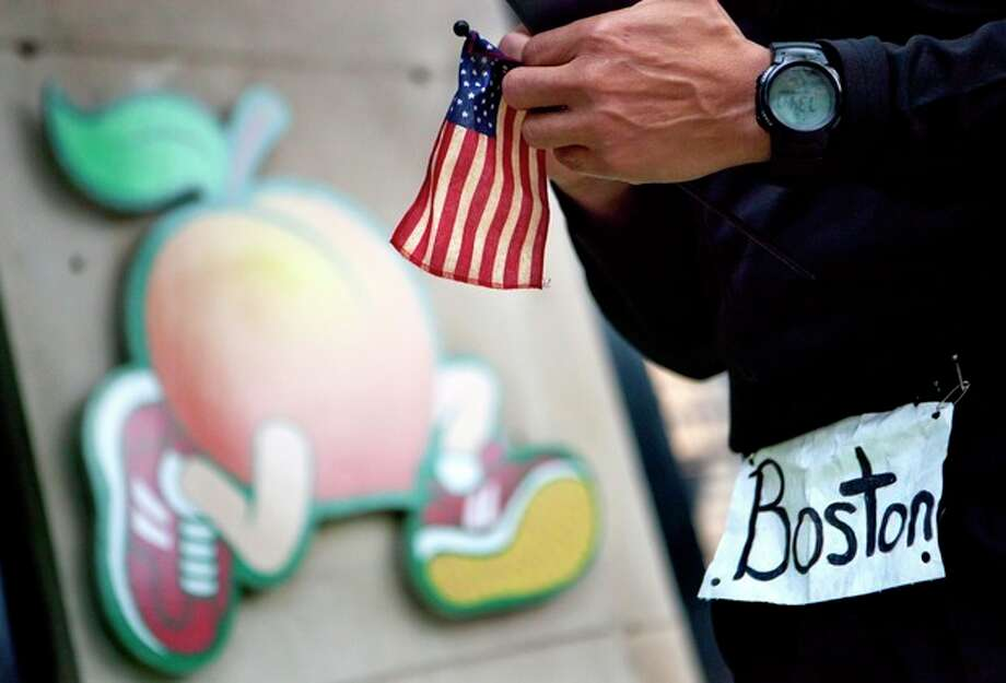 Reginald Bohannon, of Atlanta, holds a United States flag as he stands outside the Big Peach Running Co. after taking part in an organized moment of silence and memorial run to show solidarity with victims of the Boston Marathon bombing, Tuesday, April 16, 2013, in Atlanta. The explosions Monday afternoon killed at least three people and injured at least 100 others. (AP Photo/David Goldman) / AP