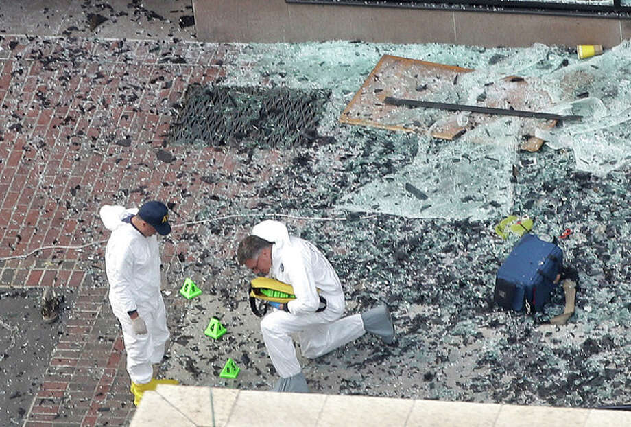 Two men in hazardous materials suits put numbers on the shattered glass and debris as they investigate the scene at the first bombing on Boylston Street in Boston Tuesday, April 16, 2013 near the finish line of the 2013 Boston Marathon, a day after two blasts killed three and injured over 170 people. The bombs that ripped through the Boston Marathon crowd were fashioned out of ordinary kitchen pressure cookers, packed with nails and other fiendishly lethal shrapnel, and hidden in duffel bags left on the ground, people close to the investigation said Tuesday. (AP Photo/Elise Amendola) / AP