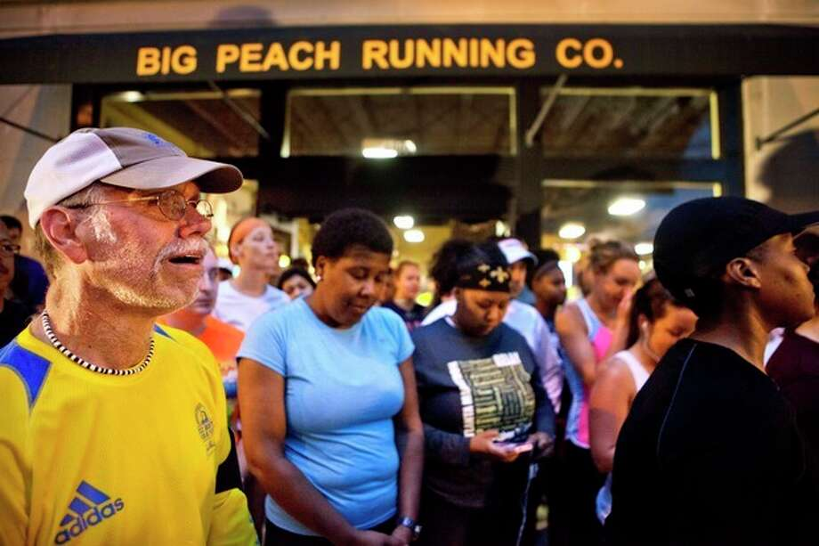 John Tackett, of Atlanta, left, weeps during an organized moment of silence and memorial run to show solidarity with victims of the Boston Marathon bombing, Tuesday, April 16, 2013, in Atlanta. The explosions Monday afternoon killed at least three people and injured at least 100 others. (AP Photo/David Goldman) / AP