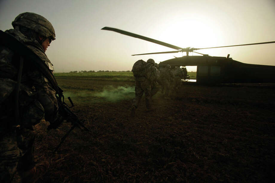U.S. Army Pvt. 1st Class David Hedge from Bealeton, Va., left, and fellow soldiers from 1st Battalion, 18th Infantry Regiment rush to a Blackhawk helicopter after a an operation to disrupt weapons smuggling in Istaqlal, north of Baghdad, Iraq, Monday, Aug. 8, 2011. (AP Photo/Maya Alleruzzo) / AP