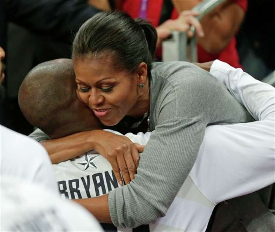 First Lady Michelle Obama hugs USA's Kobe Bryant after Team USA defeated France in a preliminary men's basketball game at the 2012 Summer Olympics, Sunday, July 29, 2012, in London. (AP Photo/Charles Krupa) / AP