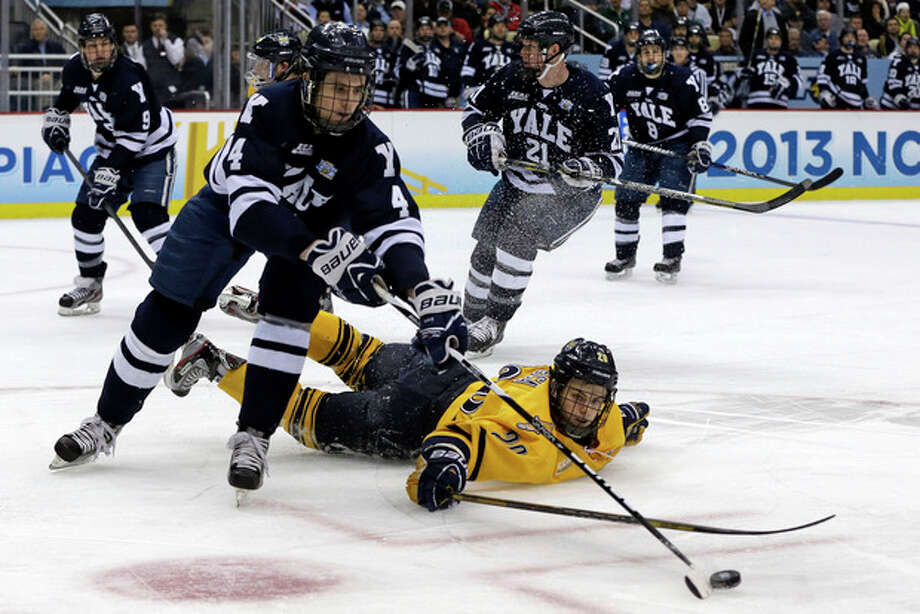 Yale's Rob O'Gara (4) clears the puck after colliding with Quinnipiac's Matthew Peca (20) during the first period of the NCAA Frozen Four men's college hockey national championship game in Pittsburgh Saturday, April 13, 2013. (AP Photo/Gene Puskar) / AP