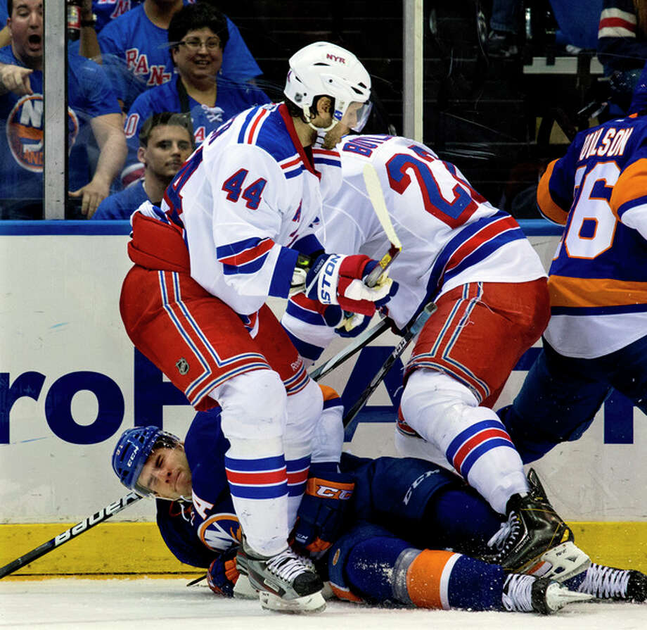 New York Islanders' John Tavares hits the ice as New York Rangers' Steve Eminger (44) and Brian Boyle (22) scramble for the puck in the second period of an NHL hockey game in Uniondale, N.Y. Saturday, April 13, 2013. (AP Photo/Craig Ruttle) / FR61802 AP