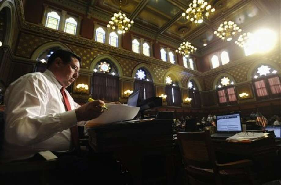 State Rep. Mike Alberts R-Woodstock, left, looks over paperwork inside Connecticut House of Representatives during the last day of session at the Capitol in Hartford, Conn., Wednesday, June 8, 2011. (AP Photo/Jessica Hill)