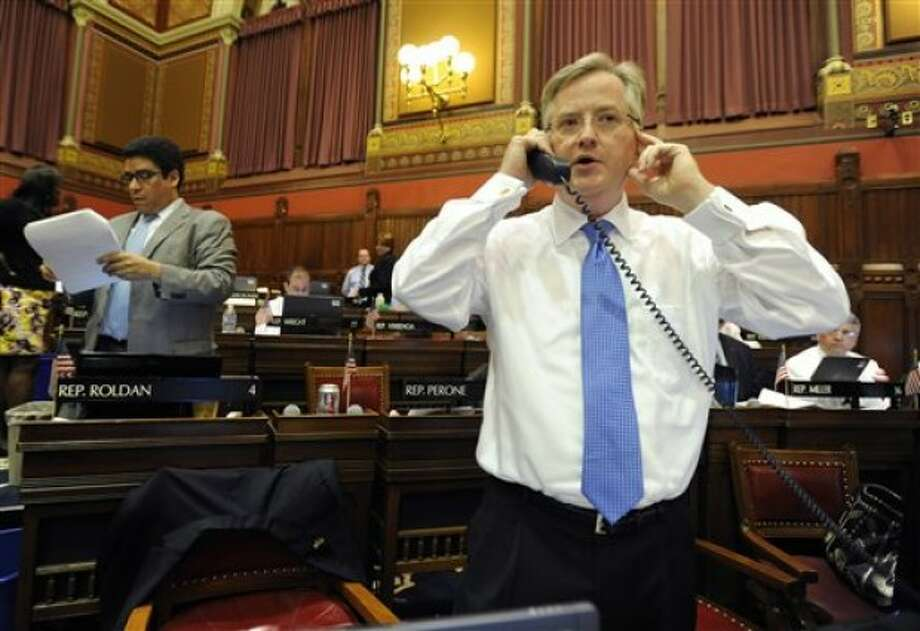 House Majority Leader Brendan Sharkey D-Hamden, right, speaks on a phone inside the Connecticut House of Representatives during the last day of session at the Capitol in Hartford, Conn., Wednesday, June 8, 2011. (AP Photo/Jessica Hill)