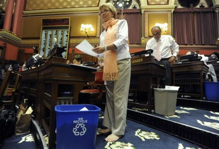 State Rep. Pam Sawyer, R-Bolton, works in her bare feet inside the Connecticut House of Representatives during the last day of session at the Capitol in Hartford, Conn., Wednesday, June 8, 2011. (AP Photo/Jessica Hill)