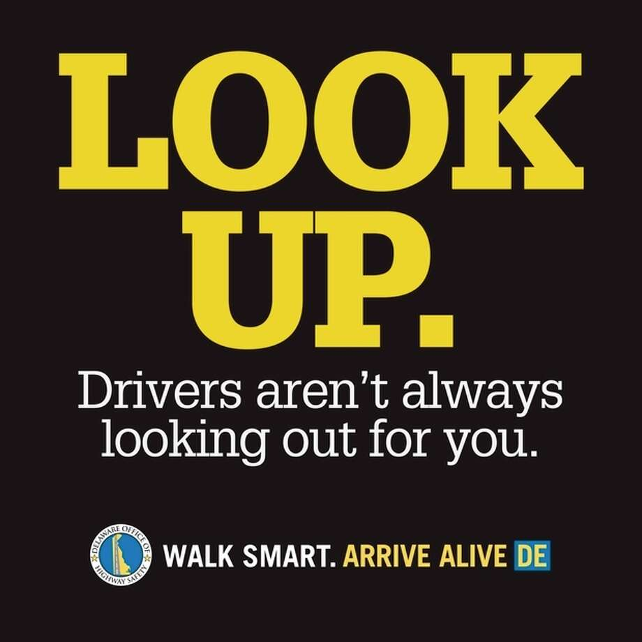 ADVANCE FOR MONDAY, JULY 30 AND THEREAFTER - This undated handout image provided by Delaware State Office of Highway Safety shows a the decal aimed at getting distracted pedestrians to look up from their mobile devices and watch where theyíre walking. The decals are 2 feet by 2 feet, made of nonskid material. Across the country on city streets, in suburban parking lots and in shopping centers, there is usually someone strolling while talking on a phone, texting with their head down, listening to music, or playing a video game. The problem isn't as widely discussed as distracted driving, but the danger is real. (AP Photo/Delaware State Office of Highway Safety) / Delaware State Office of Highway Safety