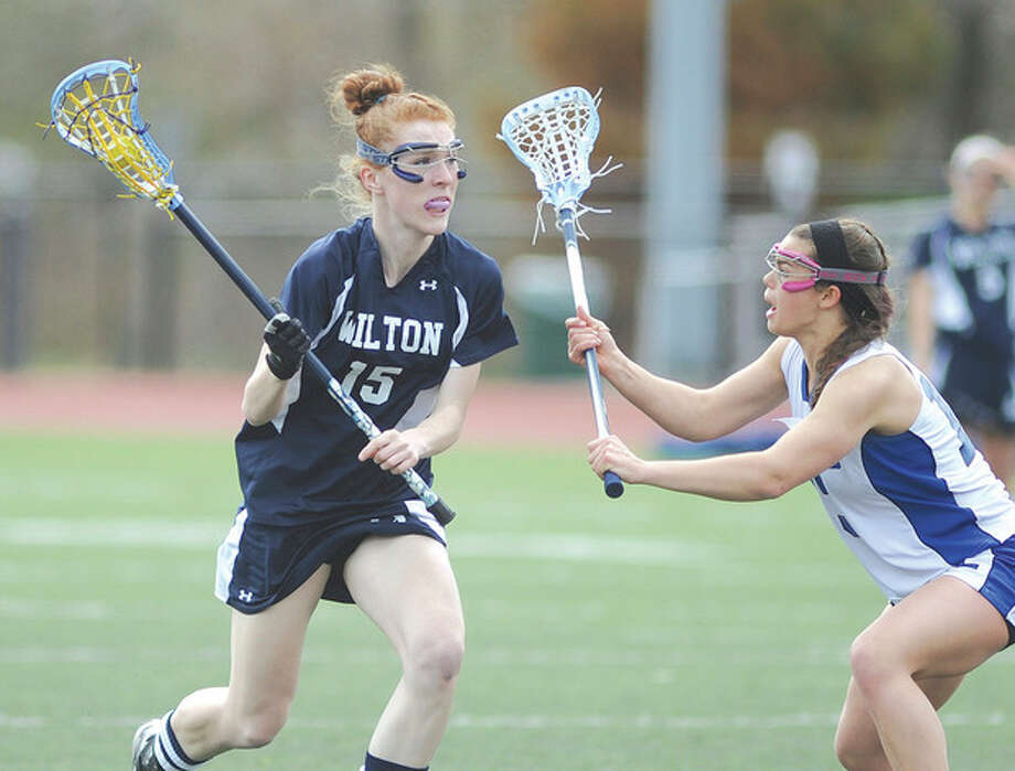 Hour photo/John NashShannon Quinlan of Wilton, left, looks past the defense of Fairfield Ludlowe's Sarah Mason to her teammates during Saturday's game at Taft Field in Fairfield.