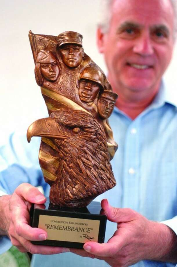 "Hour Photo/ Alex von Kleydorff. Sculptor Peter Rubino holds 'Soldier of Remembrance,"" his sculpture given by Peg Koellmer to the Wilton Police Department."