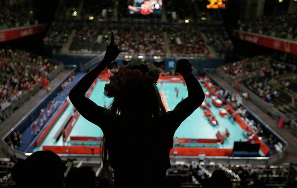 A fan cheering for Turkey celebrates as he team scores a point against China during a women's volleyball preliminary match at the 2012 Summer Olympics Monday, July 30, 2012, in London. (AP Photo/Chris O'Meara)