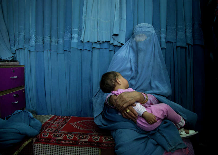 In this Thursday, April 11, 2013 photo, an Afghan woman waits with her child in front a changing room to try on a new burqa at a shop in the old town of Kabul, Afghanistan. Despite advances in women's rights, Afghanistan remains a deeply conservative country and most women continue to wear the Burqa. But tradesmen say times are changing in Kabul at least, with demand for burqas declining as young women going to school and taking office jobs refuse to wear the cumbersome garments. (AP Photo/Anja Niedringhaus) / AP