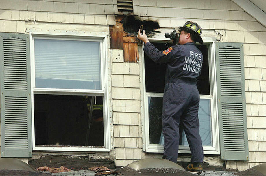 Hour Photo/Alex von Kleydorff Deputy Fire Marshal Chris Hansen takes a photo of an object of interest while checking the second floor exterior of a house on Lawrence St that caught fire Tuesday afternoon. / 2013 The Hour Newspapers