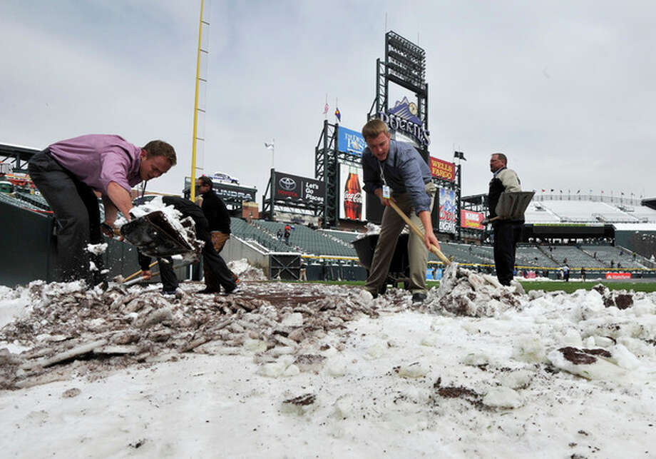 Coors Field grounds crew and stadium employees shovel snow before the start of a baseball doubleheader between the New York Mets and Colorado Rockies on Tuesday, April 16, 2013, in Denver. (AP Photo/Jack Dempsey) / FR42408 AP