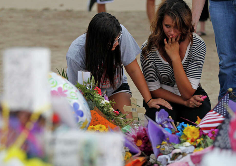 Brittani Roehr, left, from Wichita, Kan., and Chelsea Holi, from Aurora, react at the memorial across from the movie theater, Sunday, July 29, 2012 in Aurora, Colo., where twelve people were killed and more than 50 wounded in a shooting attack on July 20. (AP Photo/Alex Brandon) (AP Photo/Alex Brandon) / AP