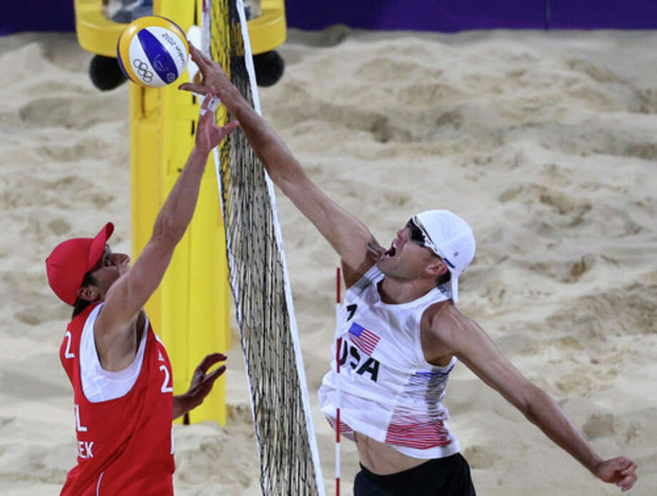 Grzegorz Fijalek, left, from Poland tries to block Jake Gibb, right, of US during their Beach Volleyball match at the 2012 Summer Olympics, Monday, July 30, 2012, in London. (AP Photo/Petr David Josek) / AP