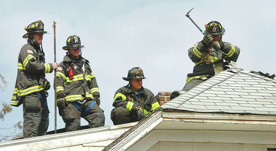 Hour photo /Alex von KleydorffFirefighter Jim Mills with Ladder Truck 2 vents the roof of a house on Lawrence St. that caught fire Tuesday afternoon. / 2013 The Hour Newspapers