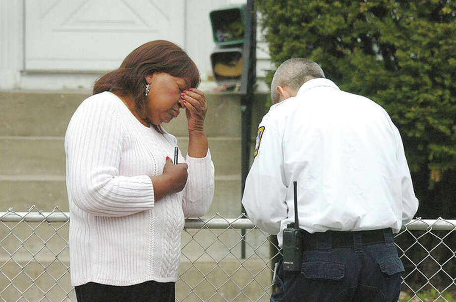 Hour Photo/Alex von Kleydorff . Nellie Mann talks with Norwalk Hospital Paramedics after her house on Lawrence St. caught fire on Tuesday. / 2013 The Hour Newspapers