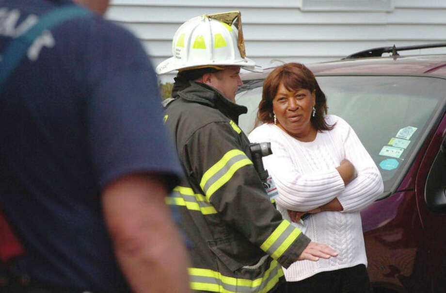 Hour Photo/Alex von Kleydorff Nellie Mann talks with Fire Personnel after her house on Lawrence St caught fire on Tuesday afternoon. / 2013 The Hour Newspapers