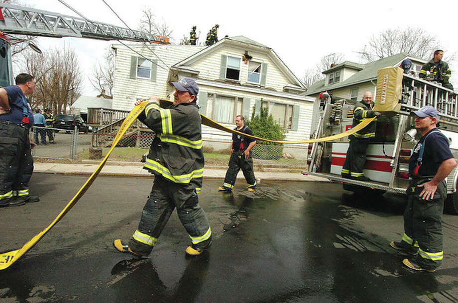 Hour Photo/Alex von Kleydorff Emergency personnel respond to a house fire on Lawrence St. Norwalk Tuesday / 2013 The Hour Newspapers