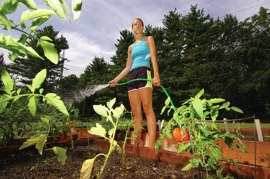 Hour photo by Alex von Kleydorff FEEDING THE PLANTS Karina Olsen waters the garden she planted at Trackside Teen Center. / 2011 The Hour Newspapers