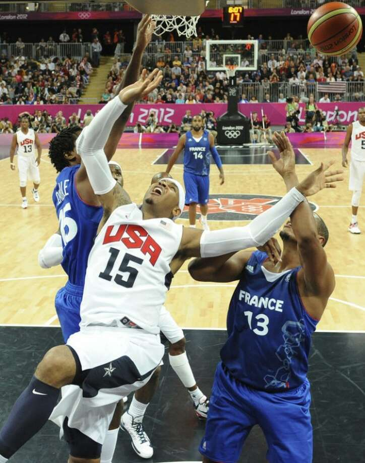 United States' forward Carmelo Anthony, center, reacts after shooting while being challenged by French forward Boris Diaw, right, during the men's basketball preliminary round group A match between the United States and France at the 2012 Summer Olympics, on Sunday, July 29, 2012 in London. (AP Photo/Mark Ralston, Pool)