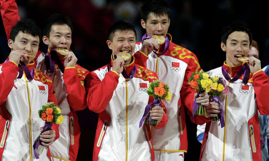 Chinese gymnasts, left to right, Feng Zhe, Guo Weiyang, Chen Yibing, Zhang Chenglong and Zou Kai bite their gold medals during the medal ceremony of the Artistic Gymnastic men's team final at the 2012 Summer Olympics, Monday, July 30, 2012, in London. (AP Photo/Julie Jacobson) / AP