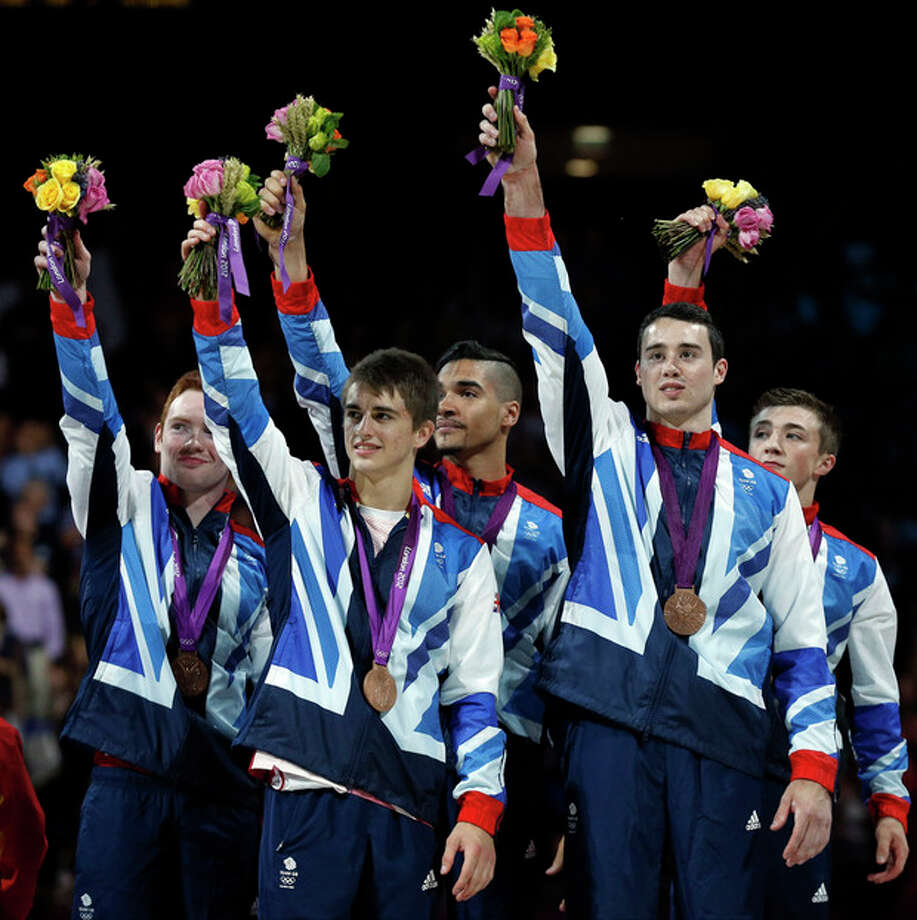 Great Britain's gymnasts, left to right, Daniel Purvis, Max Whitlock, Louis Smith, Kristian Thomas and Sam Oldham wave from the podium during the medal ceremony of the Artistic Gymnastic men's team final at the 2012 Summer Olympics, Monday, July 30, 2012, in London. Britain won the bronze. (AP Photo/Matt Dunham) / AP