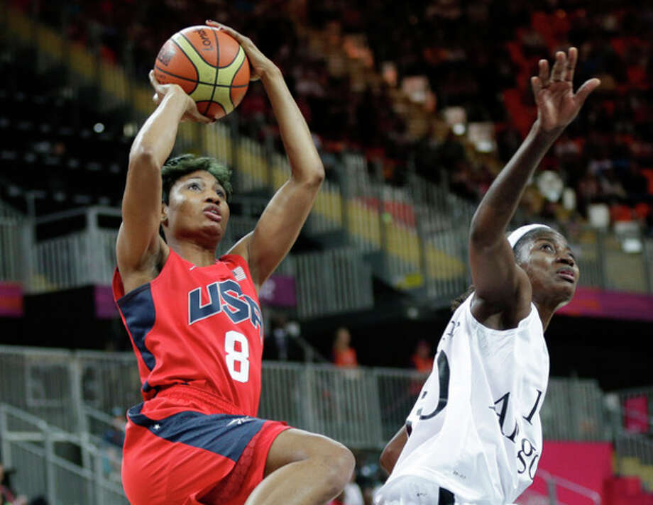 USA's Angel McCoughtry (8) shoots over Angola's Sonia Guadalupe, right, during the first half of a preliminary women's basketball game at the 2012 Summer Olympics, Monday, July 30, 2012, in London. (AP Photo/Eric Gay) / AP