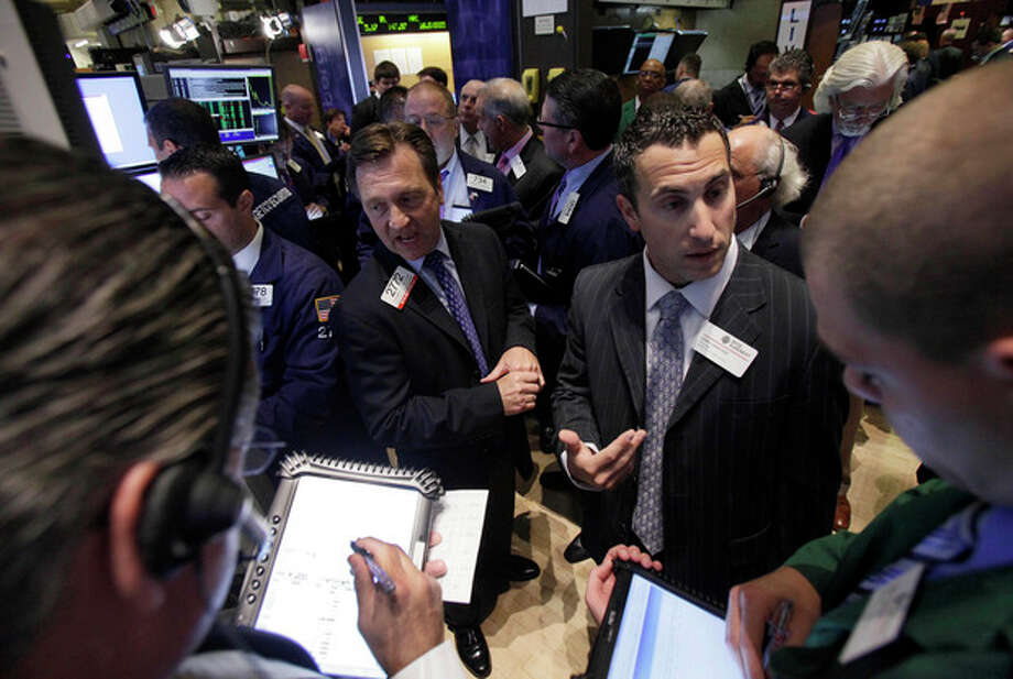 FILE - In a Thursday, July 26, 2012 photo, traders gather at a post on the floor of the New York Stock Exchange during the IPO of Northern Tier Energy. U.S. stocks crept higher in early trading Monday, July 30, 2012 on Wall Street following big gains last week. (AP Photo/Richard Drew, File) / AP