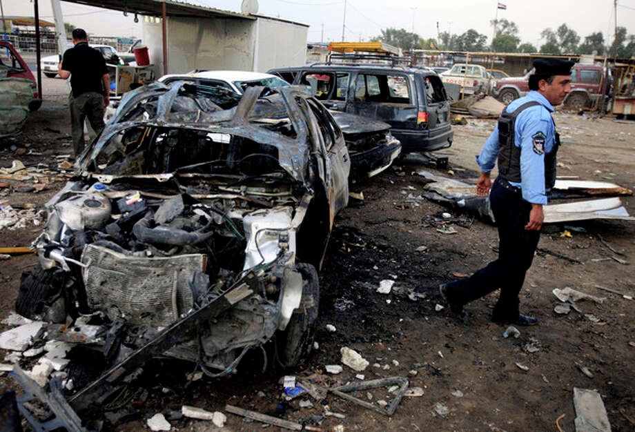 A policeman inspects the aftermath of a car bomb attack at a used cars dealers parking lot in Habibiya neighborhood of eastern Baghdad, Iraq, Tuesday, April 16, 2013. Less than a week before Iraqis in much of the country are scheduled to vote in the country's first elections since the 2011 U.S. troop withdrawal, a series of attacks across Iraq on Monday, many involving car bombs, has killed and wounded dozens of people, police said. (AP Photo/Karim Kadim) / AP