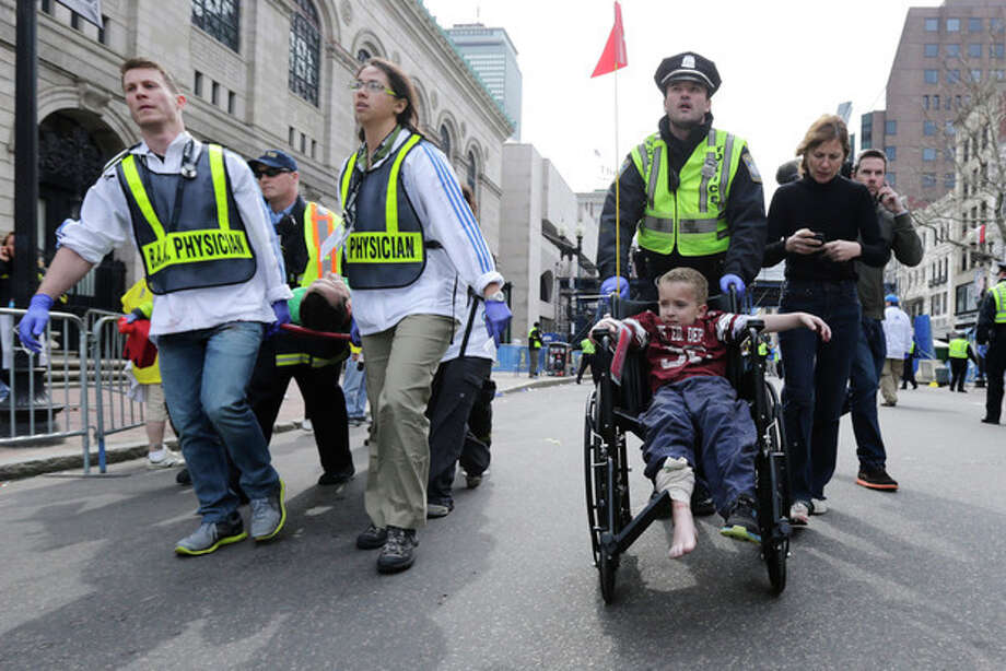 A Boston police officer wheels in injured boy down Boylston Street as medical workers carry an injured runner following an explosion during the 2013 Boston Marathon in Boston, Monday, April 15, 2013. Two explosions shattered the euphoria at the marathon's finish line on Monday, sending authorities out on the course to carry off the injured while the stragglers were rerouted away from the smoking site of the blasts. (AP Photo/Charles Krupa) / AP