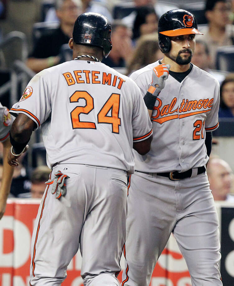 Baltimore Orioles' Nick Markakis, right, greets Wilson Betemit after Betemit scored on a hit by Omar Quintanilla during the fifth inning of a baseball game against the New York Yankees, Monday, July 30, 2012, at Yankee Stadium in New York. (AP Photo/Seth Wenig) / AP