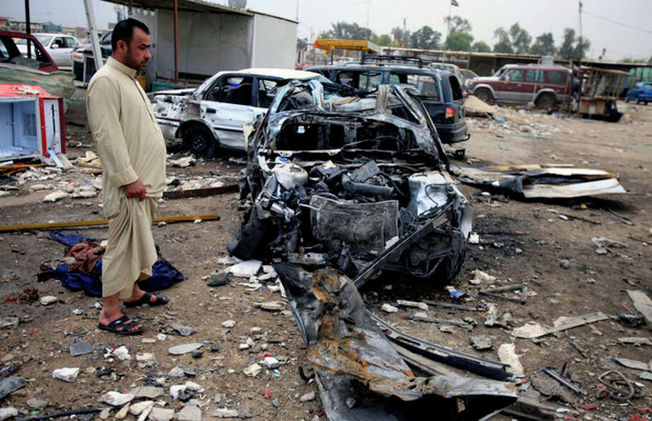 An Iraqi man inspects the aftermath of a car bomb attack at a used cars dealers parking lot in Habibiya neighborhood of eastern Baghdad, Iraq, Tuesday, April 16, 2013. Less than a week before Iraqis in much of the country are scheduled to vote in the country's first elections since the 2011 U.S. troop withdrawal, a series of attacks across Iraq on Monday, many involving car bombs, has killed and wounded dozens of people, police said. (AP Photo/ Karim Kadim) / AP
