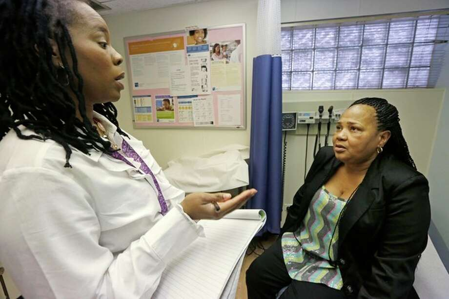 ADVANCE FOR WEDNESDAY, APRIL 17 AND THEREAFTER - In this March 11, 2013 photo, Michelle Adams, left, a case manager at the West Division Family Health Center in Chicago, speaks with Shavonne Bullock, a recovering heroin addict during an appointment. Bullock, who has been drug free since 2006 when she started treatment at the center, pays for her own treatment because she's uninsured. Millions of Americans will gain insurance coverage for drug addiction and alcoholism treatment when the national health overhaul takes effect next year, and some experts predict the change will help thousands of people get clean and sober. (AP Photo/M. Spencer Green) / AP