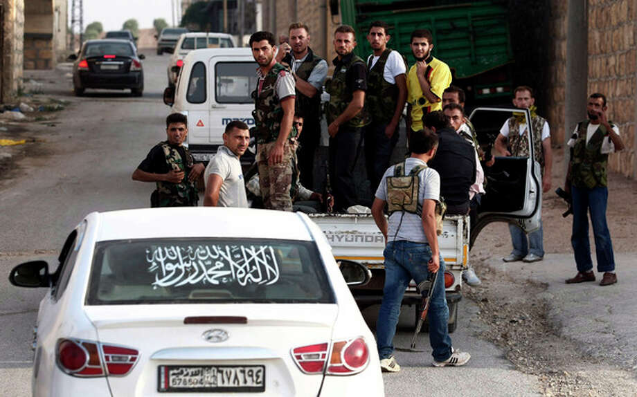 In this Sunday, July 29, 2012 photo, Free Syrian Army soldiers are seen at the border town of Azaz, some 20 miles (32 kilometers) north of Aleppo, Syria. The U.N. said 200,000 Syrians have fled the embattled city of Aleppo since intense clashes between regime forces and rebels began 10 days ago. The government forces turned mortars, tank and helicopter gunships against rebel positions on Monday, July 30, 2012. (AP Photo/Turkpix) / AP