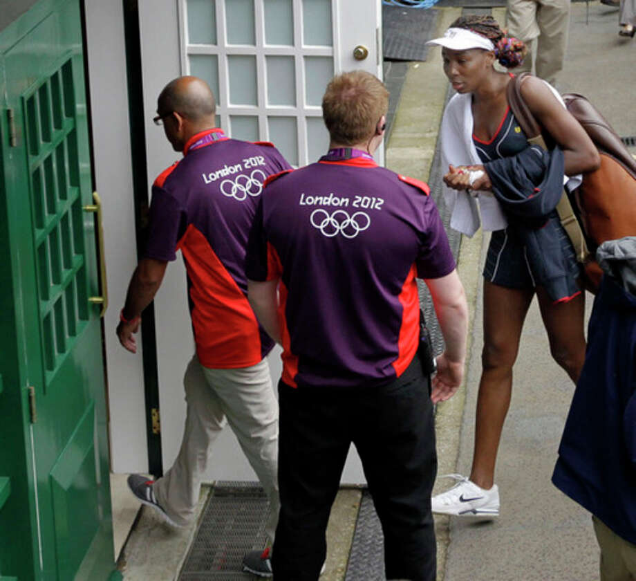 Venus Williams of the United States leaves Centre Court after defeating Aleksandra Wozniak of Canada at the All England Lawn Tennis Club in Wimbledon, London at the 2012 Summer Olympics, Tuesday, July 31, 2012. (AP Photo/Elise Amendola) / AP