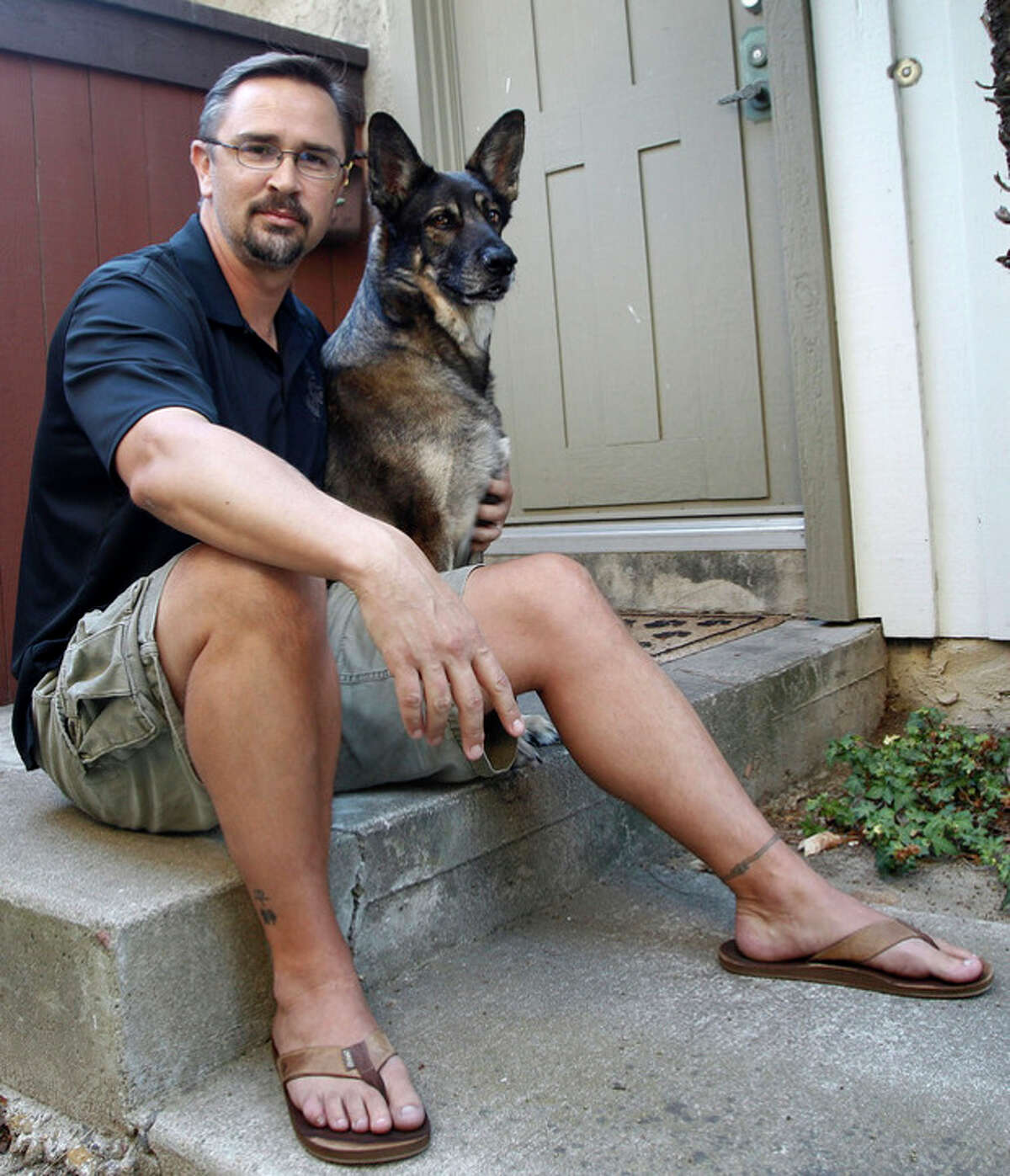"""In this Monday, July 23, 2012 photo, retired U.S. Marine Todd Kennedy poses on his front stoop with his pet, Malcolm, in San Diego. Kennedy served two tours in Iraq. He no longer follows the news there, focusing instead on studying history and anthropology at San Diego State University. ?""""In any war there are lessons learned. Any war has its skeletons. Any war has its debates, repercussions, its conspiracies. Regardless of whether it was right or wrong to go in to there, for me personally, it's not something I did a lot of dwelling on ... The nation called on me, so it was something I had to do."""" (AP Photo/Lenny Ignelzi)"""